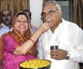 Haryana Chief Minister Bhupinder Singh Hooda being offered sweets by his wife Asha Hooda