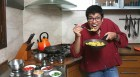 <b>Yum maro yum</b> The author in her kitchen, tucking into good ol' poha