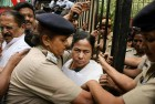 Security women protect West Bengal Chief Minister Mamata Banerjee during a protest by SFI activists on her arrival at Yojana Bhavan in New Delhi.