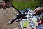 In this Oct 17, 2012 photo, Wilfredo Yanes, reflected on a mirror of his motorcycle, shows pictures of his late son Ebed Jaasiel Yanes, 15, at the site where he was shot dead allegedly by soldiers in Tegucigalpa, Honduras. According to his relatives, Yanes was killed by soldiers early Sunday, May 27, when he was riding a motorcycle, near a military checkpoint.