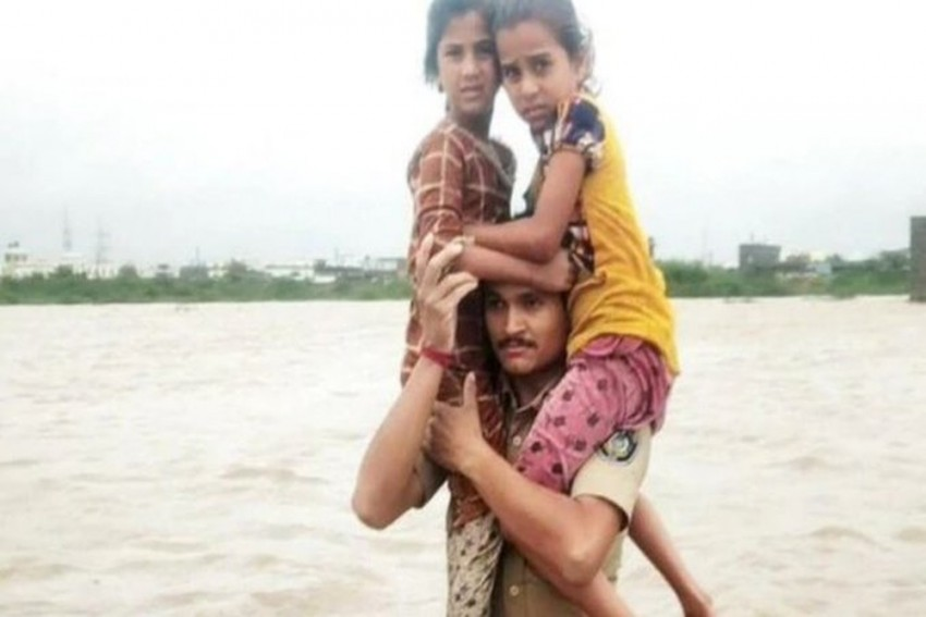 Gujarat Cop Praised For Carrying 2 Kids On Shoulders In Knee-Deep Flood Water