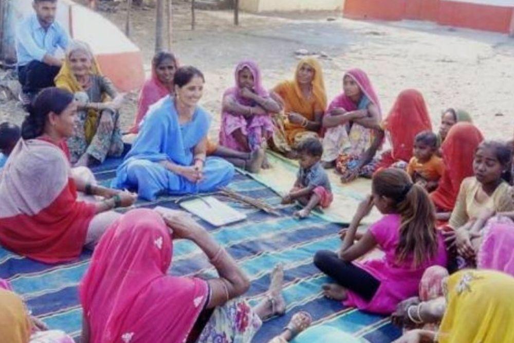 Village women listening to health workers