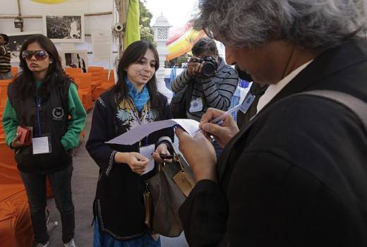 Author Romesh Gunesekera signs a petition to reconsider the ban on Salman Rushdie's <i>The Satanic Verses</i> aswriter Anni Zaidi, looks on at the Jaipur Literature Festival, in Jaipur.