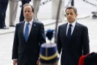 Outgoing French President Nicolas Sarkozy, right, and President-elect Francois Hollande observe a minute of silence at the Tomb of the Unknown Soldier during commemorations at the Arc de Triomphe in Paris, marking the anniversary of the end of World War II in Europe.