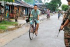 Locals cycle past armymen patrolling in Kokrajhar town