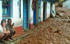 <b>Drowned in brown</b> Villagers sit outside their homes in a mud-inundated street