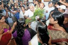 Women activists present bouquets to Kerala CM Oommen Chandy after the new excise policy