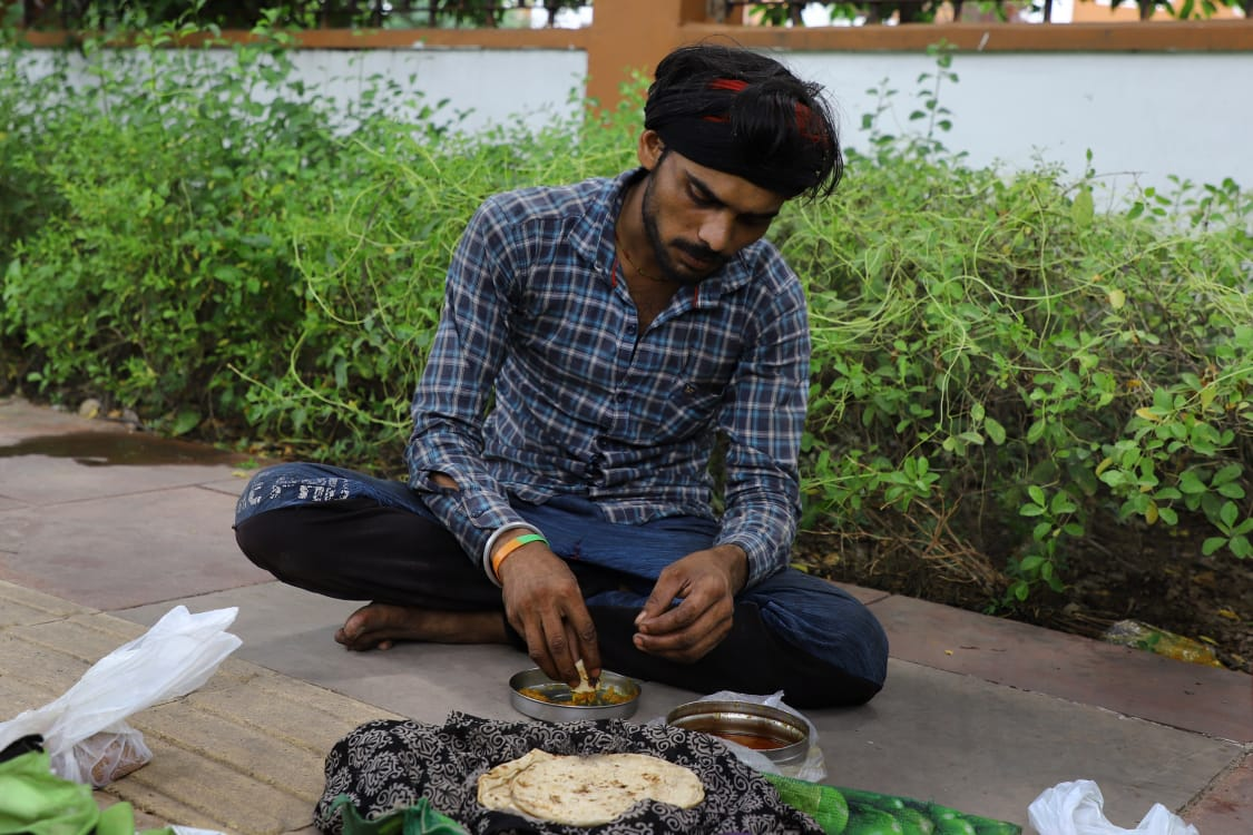 A man has his lunch at footpath in New Delhi. (Image Credit: Suresh Pandey)