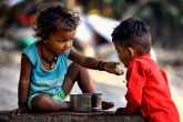 A child feeds another child in New Delhi (Image Credit: Suresh Pandey)