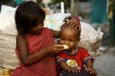 Child feeding Banana to another in Ghaziabad. (Image credit: Suresh Kumar Pandey)