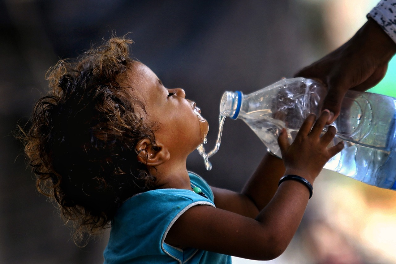 A child happily drinks water after being offered by another person in Delhi ( Image Credit: Suresh Kumar Pandey)