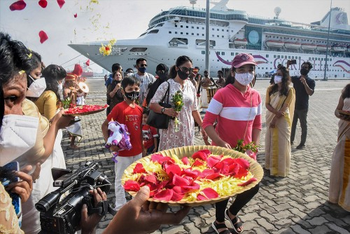 Artists welcome tourists as they arrive to board Cordelia cruise ship on their way from Mumbai to Lakshadweep, during a Kerala Tourism event, in...