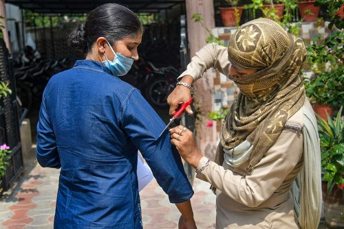 A security personnel cuts the sleeve of a candidate's cloth for security purposes during the Rajasthan Eligibility Examination for Teachers (REET),...